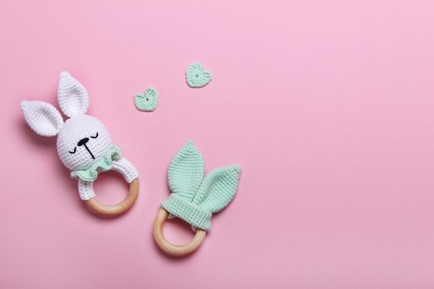 Brinquedos de madeira eco bebê, pufe e mordedores em fundos rosa com espaço de cópia. vista superior, plana leiga.