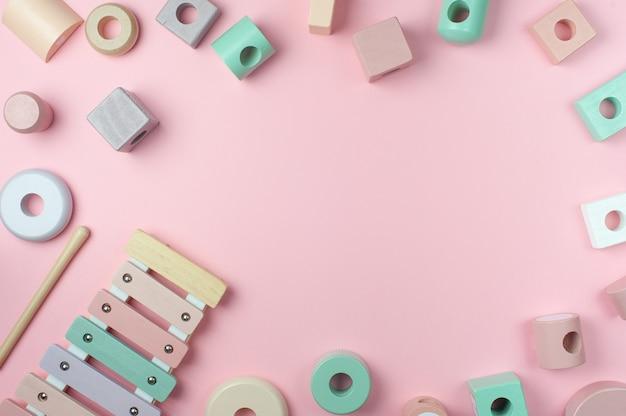Brinquedos de madeira em tons pastel sobre fundo rosa. postura plana. vista do topo. lugar para texto