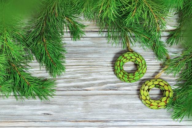 Brinquedos de madeira redondos em ramos da árvore de natal no fundo de madeira.