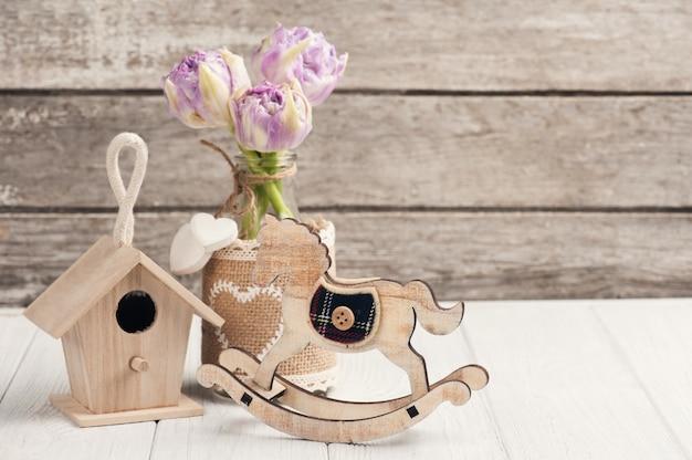 Brinquedos de madeira, tulipas cor de rosa e cavalo de balanço