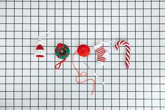 Brinquedos de malha de natal feitos à mão em crochê de crochê, donut e meia em fundo branco quadriculado