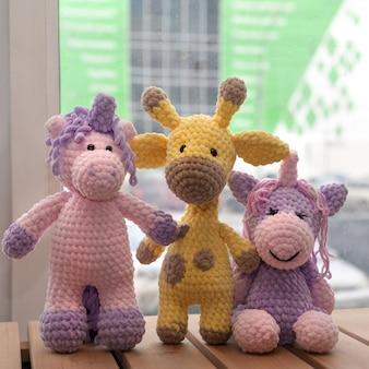 Brinquedos de malha feitos à mão. girafa amarela e dois unicórnios.
