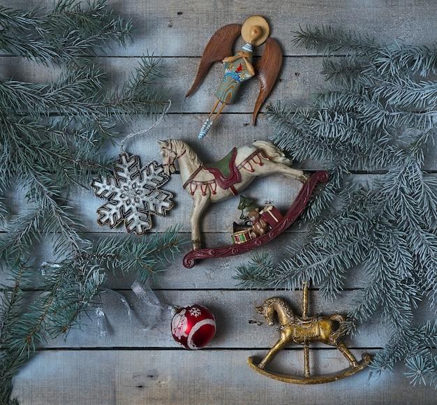 Brinquedos de natal antigos, galhos de árvores de abeto em fundo rústico de madeira gelada