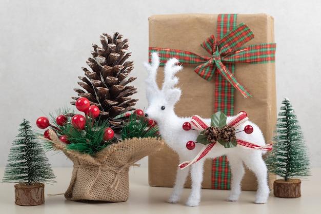Brinquedos de natal com caixa de papel e decoração em superfície branca