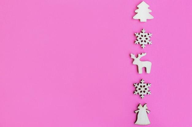 Brinquedos de natal de madeira em fundo rosa, vista superior, configuração plana, conceito mínimo de ano novo, design ou cartão postal