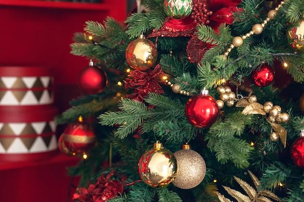 Brinquedos de natal de ouro e vermelhos, bolas, guirlandas em um galho de abeto em fundo vermelho escuro.