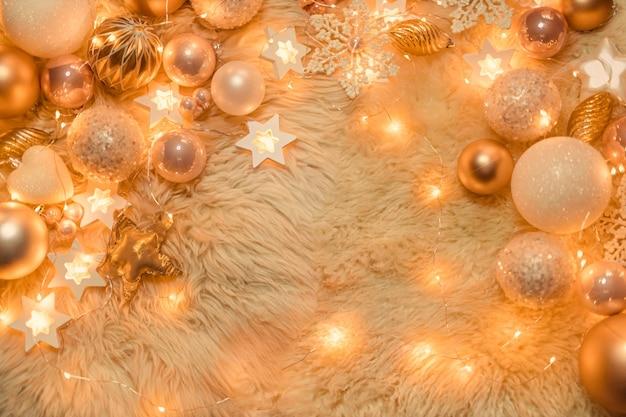 Brinquedos de natal dourados e rosa no meio de luzes acesas de guirlandas, flat lay, vista superior, copie o espaço.
