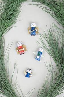 Brinquedos de natal e galho em superfície bege
