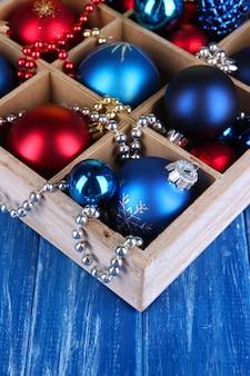 Brinquedos de natal em caixa em close-up de mesa de madeira