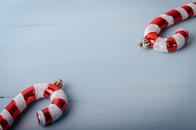 Brinquedos de natal em formato de bengala em uma superfície de madeira rachada com um espaço de cópia