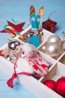 Brinquedos de natal em uma caixa de madeira sobre um fundo azul de madeira