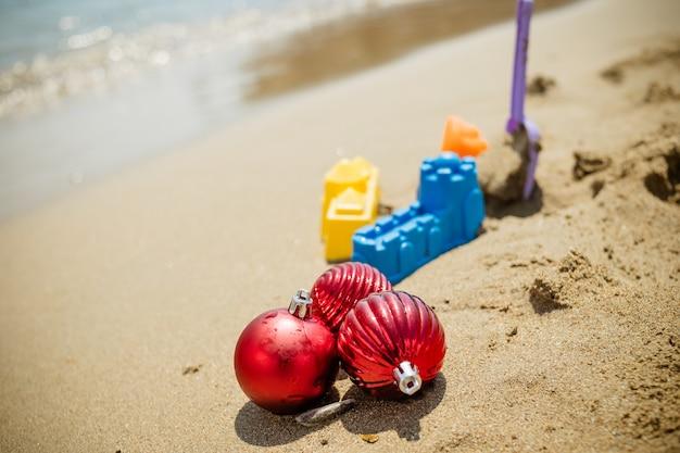 Brinquedos de natal, enfeites na praia de areia contra o oceano.