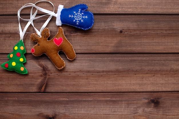 Brinquedos de natal feitos de feltro - uma árvore de natal verde, um cervo marrom e uma luva azul