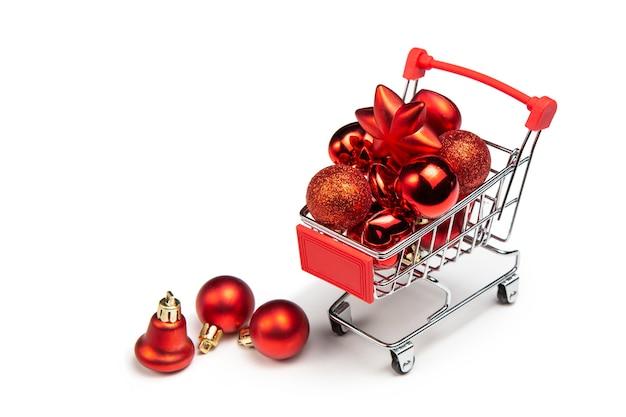 Brinquedos de natal na cesta do comprador. carrinho de compras completo. bolas, sinos ao lado do carrinho de compras.