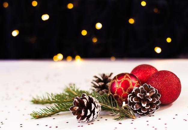 Brinquedos de natal vermelhos e pinhas repousam sobre um fundo branco com bokeh