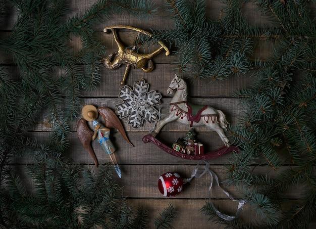 Brinquedos de natal vintage, galhos de árvores de abeto em uma mesa rústica de madeira