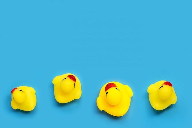 Brinquedos de pato amarelo sobre fundo azul. conceito de banho de crianças.
