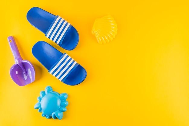 Brinquedos de praia e chinelos azuis sobre fundo amarelo
