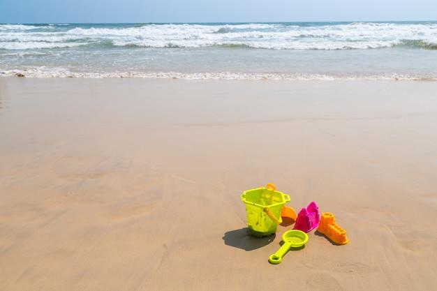 Brinquedos de praia infantil - baldes, pá e pá na areia em um dia ensolarado