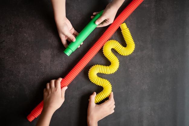Brinquedos de tubo sensorial anti-stress nas mãos de uma criança. crianças felizes brincam com um brinquedo poptube em uma mesa preta. crianças segurando e brincando de tubos de pipoca multicoloridos brilhantes, tendência 2021 ano