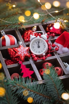 Brinquedos de vidro vermelho e branco de natal, despertador, chapéu de papai noel na cesta com galhos de árvores de abeto