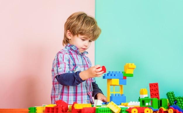Brinquedos educativos para crianças pequenas. menino brincando com montes de construtor de blocos de plástico coloridos. menino brincando com blocos de construção no jardim de infância. criança brincando com blocos de brinquedos coloridos.