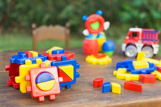 Brinquedos feitos com blocos de plástico coloridos na mesa de madeira