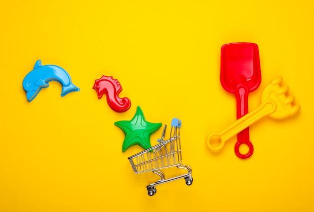 Brinquedos infantis de praia ou brinquedos de caixa de areia e carrinho de compras em amarelo