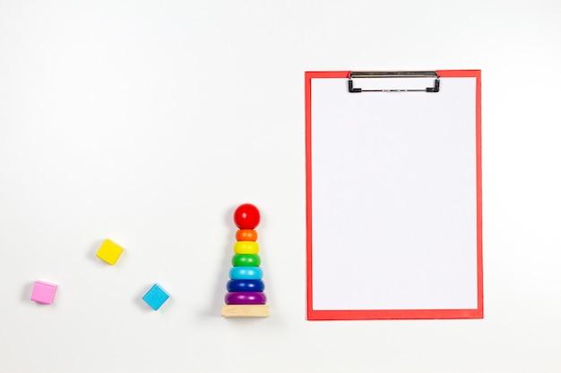 Brinquedos infantis e uma prancheta vermelha com uma folha de papel em branco no fundo branco