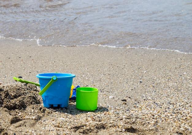 Brinquedos infantis em uma praia de areia na praia. férias com uma criança no mar em países do sul