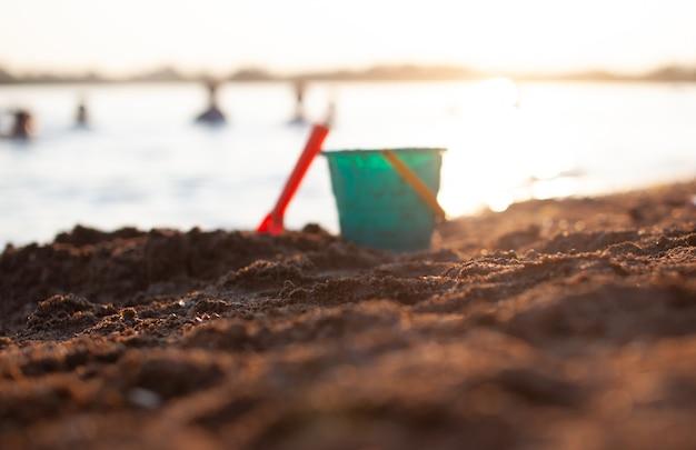 Brinquedos infantis para brincar na areia. balde de plástico e ancinho na praia ao pôr do sol. o conceito de verão, férias em família e férias. o balde está fora de foco. foco na areia