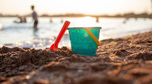 Brinquedos infantis para brincar na areia. balde de plástico e ancinho na praia ao pôr do sol. o conceito de verão, férias em família e férias.