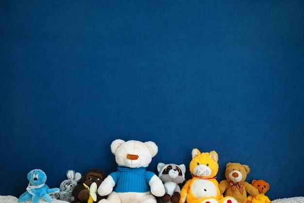 Brinquedos macios em uma parede azul com copyspace