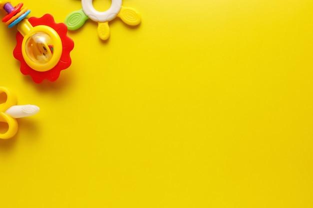 Brinquedos plásticos coloridos e vários para bebês em um fundo amarelo.