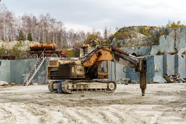 Britadeira hidráulica montada em escavadeira fica em uma pedreira para a extração de mármore