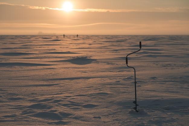 Broca de gelo. mar congelado ao fundo. paisagem com o tema da pesca de inverno.