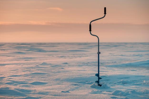 Broca de gelo para pesca. mar congelado no fundo