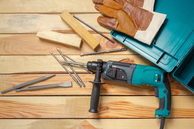 Broca de martelo elétrica encontra-se em uma mesa de madeira