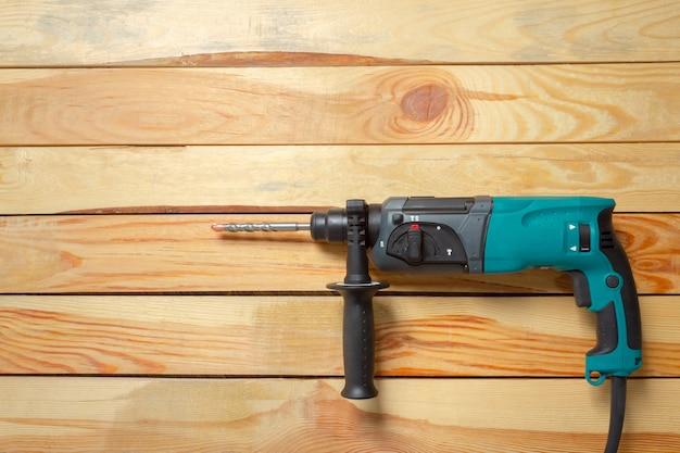 Broca de martelo elétrico encontra-se em uma mesa de madeira