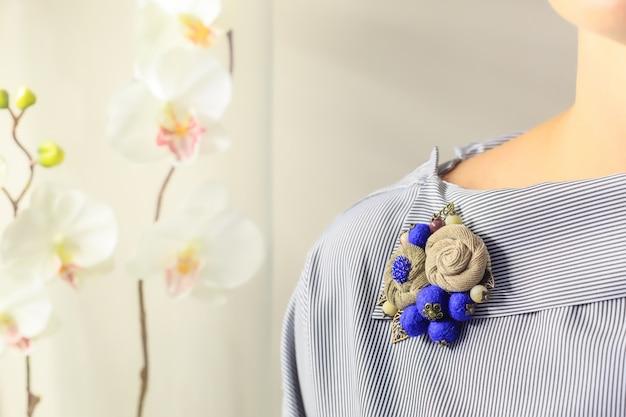Broche artesanal em forma de flores cor bege e azul é anexado à blusa feminina