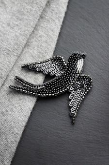 Broche bordado com conta de semente em forma de pássaro andorinha preto sobre fundo cinza e preto