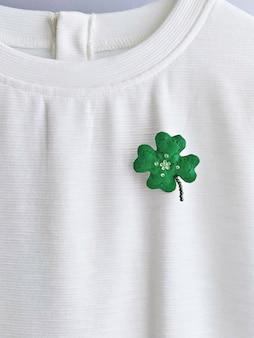 Broche de folha de trevo feito à mão na camiseta branca. conceito de comemoração do dia de são patrício