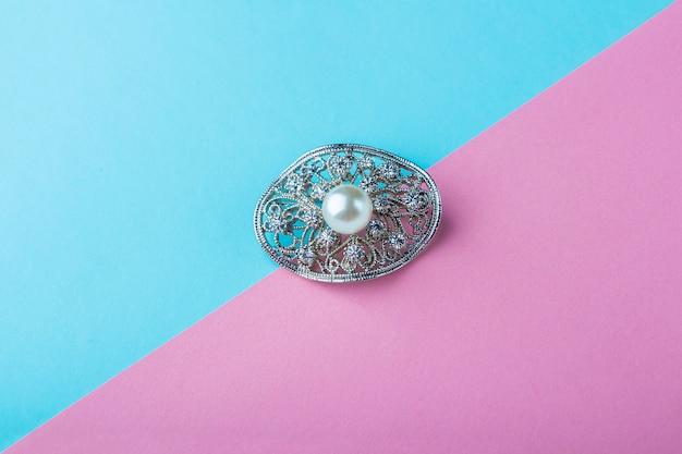 Broche de joias de pérolas vintage em fundo azul rosa. presente elegante para mulher.