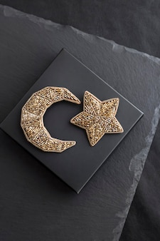 Broches bordados em contas de sementes em forma de lua e estrela no fundo da caixa preta