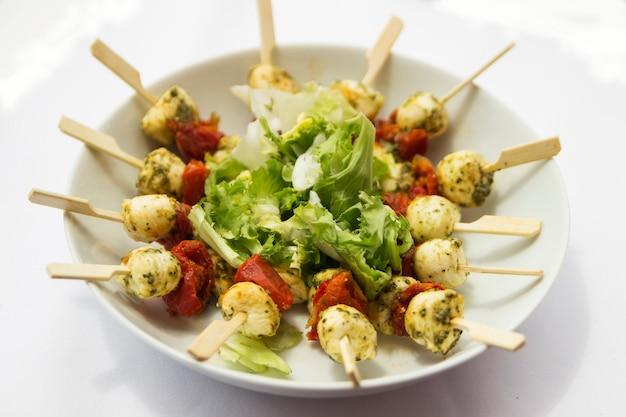 Brochette de camarão e tomate seco com salada