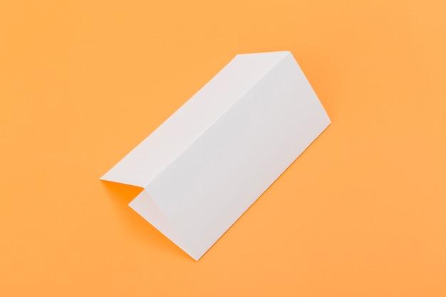 Brochura de retângulo dobrado na mesa