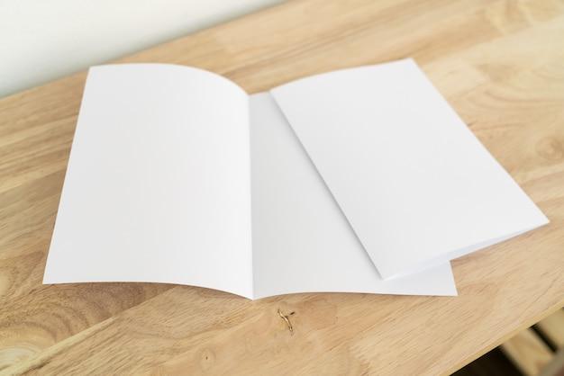 Brochuras de dobra a4 na mesa de madeira