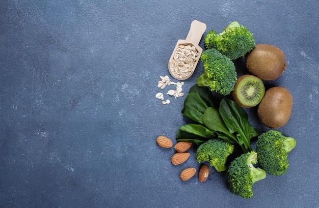 Brócolis, abacate, espinafre, kiwi, aveia e amêndoa sobre fundo azul concreto de mesa de pedra. vista do topo