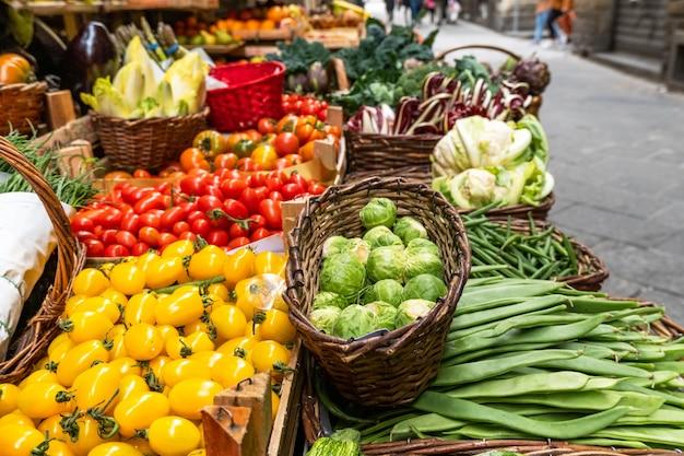 Brócolis, abobrinha, feijão verde, couve de bruxelas e tomates vermelhos em cestas no mercado local.