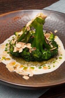 Brócolis com molho, pasta de espinafre e pétalas de amêndoa